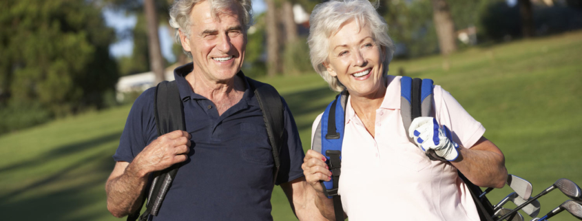 senior community golf players carrying bags